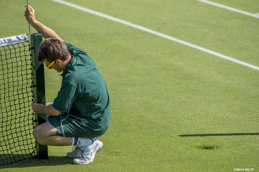 """A grounds crew worker measures a net at the All England Lawn and Tennis Club in London, England Saturday, June 21, 2014 during the 2014 Championships Wimbledon."""