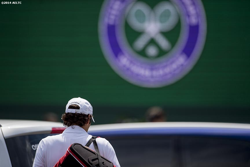 """Roger Federer walks toward a car as he leaves the All England Lawn and Tennis Club in London, England Sunday, June 22, 2014 during the 2014 Championships Wimbledon."""