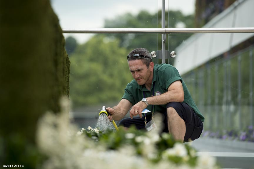 """A grounds crew member waters flowers at the All England Lawn and Tennis Club in London, England Sunday, June 22, 2014 during the 2014 Championships Wimbledon."""