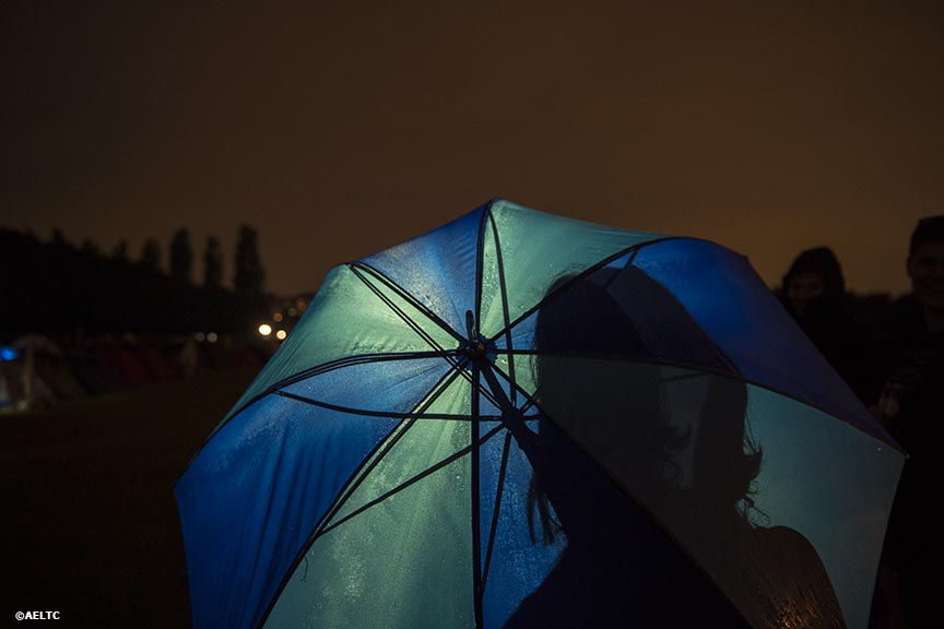 """A fan stands under an umbrella as she waits in the queue to enter the grounds at the All England Lawn and Tennis Club in London, England Thursday, June 26, 2014 during the 2014 Championships Wimbledon."""