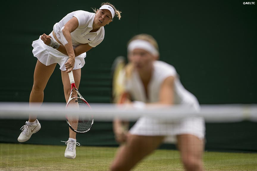 """Lucie Hradecka serves alongside partner Michaella Krajicek during a doubles match aganst Flavia Pennetta and Samantha Stosur at the All England Lawn and Tennis Club in London, England Friday, June 27, 2014 during the 2014 Championships Wimbledon."""