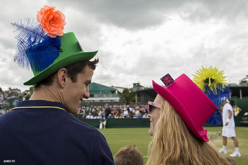"""Fans wear hats as they watch a match on the outer courts at the All England Lawn and Tennis Club in London, England Friday, June 27, 2014 during the 2014 Championships Wimbledon."""