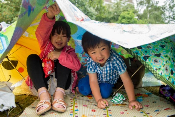 """""""Young fans peek out from underneath a blanket during a rain delay at the All England Lawn and Tennis Club in London, England Saturday, June 28, 2014 during the 2014 Championships Wimbledon."""""""