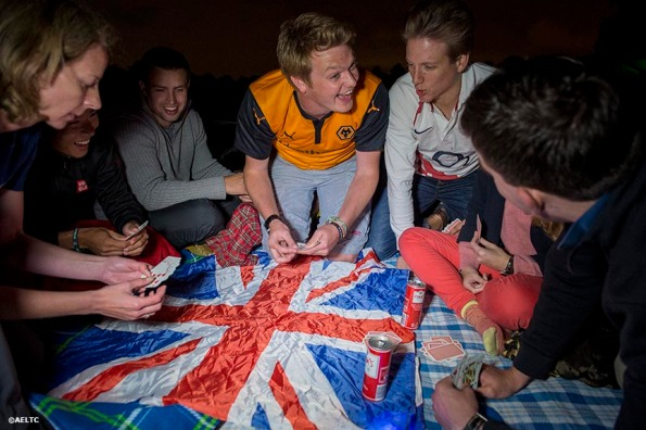 """""""Fans play cards on top of a British flag as they camp out in the queue at the All England Lawn and Tennis Club in London, England Saturday, June 28, 2014 during the 2014 Championships Wimbledon."""""""