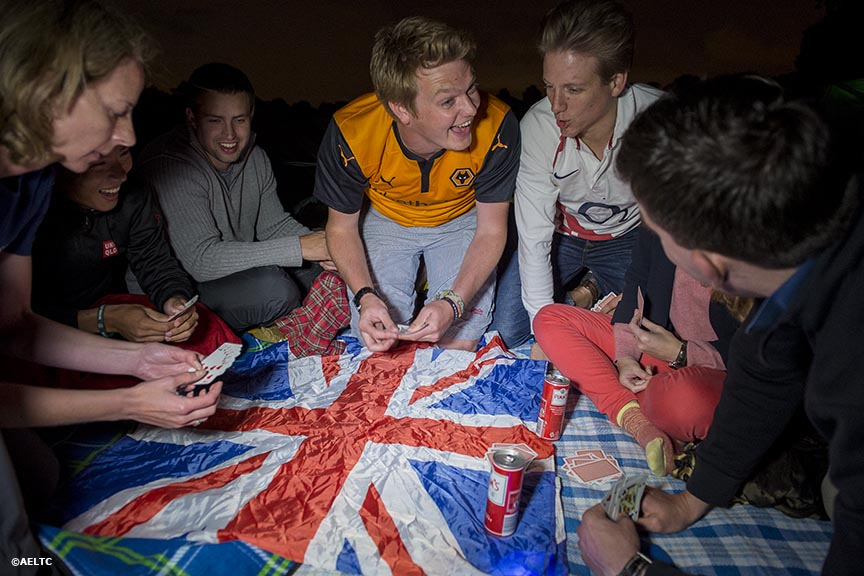 """Fans play cards on top of a British flag as they camp out in the queue at the All England Lawn and Tennis Club in London, England Saturday, June 28, 2014 during the 2014 Championships Wimbledon."""