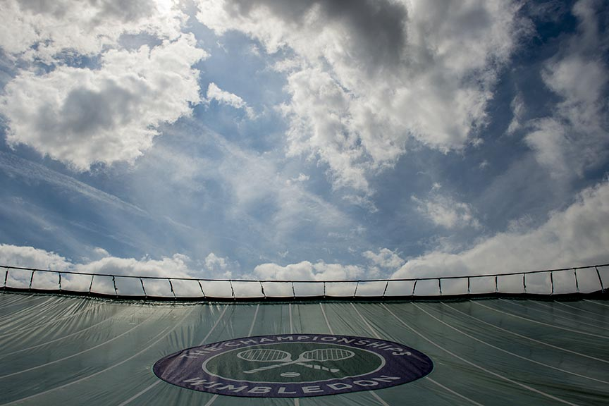"""A tarp covers No. 1 court during a rain delay at the All England Lawn and Tennis Club in London, England Monday, June 30, 2014 during the 2014 Championships Wimbledon."""