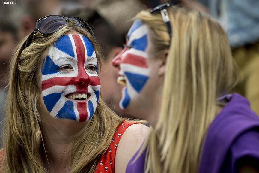 """Fans with their faces painted laugh as they watch a match between Andy Murray and Kevin Anderson on Centre Court at the All England Lawn and Tennis Club in London, England Monday, June 30, 2014 during the 2014 Championships Wimbledon."""