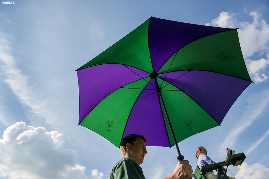 """A grounds staff member holds an umbrella on the outer courts at the All England Lawn and Tennis Club in London, England Tuesday, June 24, 2014 during the 2014 Championships Wimbledon."""