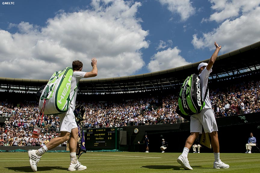 """Andy Murray and Blaz Rola wave to the crowd as they exit No. 1 Court at the All England Lawn and Tennis Club in London, England Tuesday, June 24, 2014 during the 2014 Championships Wimbledon."""