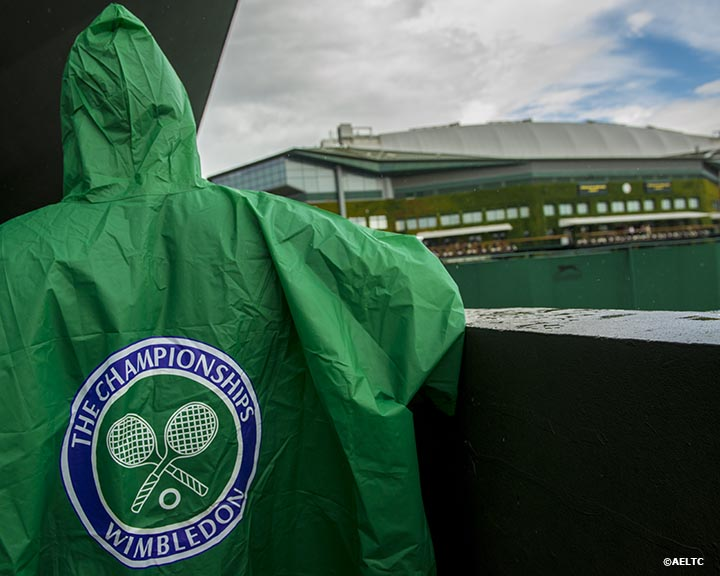 """A fan wears a Wimbledon rain coat during a rain delay at the All England Lawn and Tennis Club in London, England Saturday, June 28, 2014 during the 2014 Championships Wimbledon."""