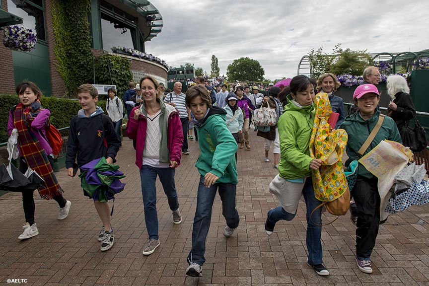 """Fans run toward the outer courts as play begins after a rain delay at the All England Lawn and Tennis Club in London, England Saturday, June 28, 2014 during the 2014 Championships Wimbledon."""
