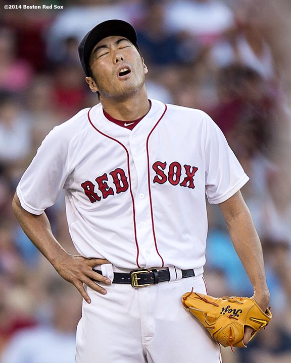 """Boston Red Sox pitcher Koji Uehara reacts after giving up a game tying home run during the ninth inning of a game against the Chicago White Sox Thursday, July 10, 2014 at Fenway Park in Boston, Massachusetts."""