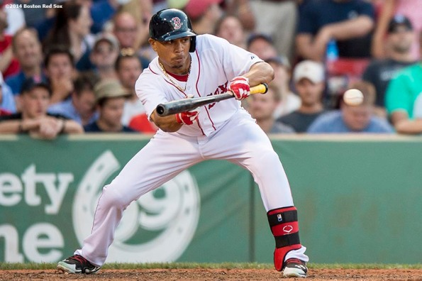 """""""Boston Red Sox right fielder Mookie Betts hits a sacrifice bunt during the tenth of a game against the Chicago White Sox 4-3 Thursday, July 10, 2014 at Fenway Park in Boston, Massachusetts."""""""