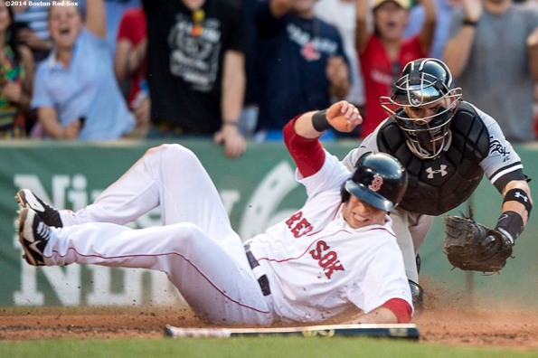 """""""Boston Red Sox pinch hitter Daniel Nava slides into home plate as he scores the game winning run during the tenth inning to defeat the Chicago White Sox 4-3 Thursday, July 10, 2014 at Fenway Park in Boston, Massachusetts."""""""