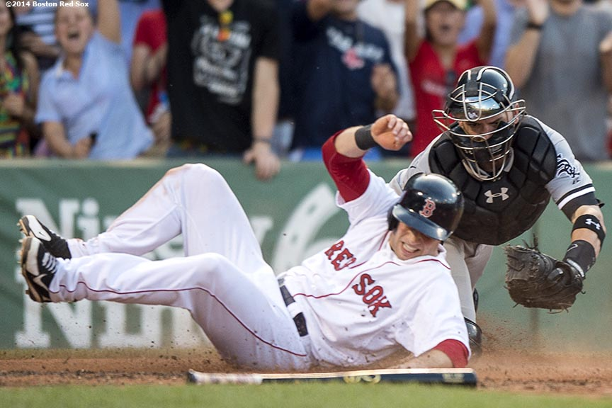 """Boston Red Sox pinch hitter Daniel Nava slides into home plate as he scores the game winning run during the tenth inning to defeat the Chicago White Sox 4-3 Thursday, July 10, 2014 at Fenway Park in Boston, Massachusetts."""