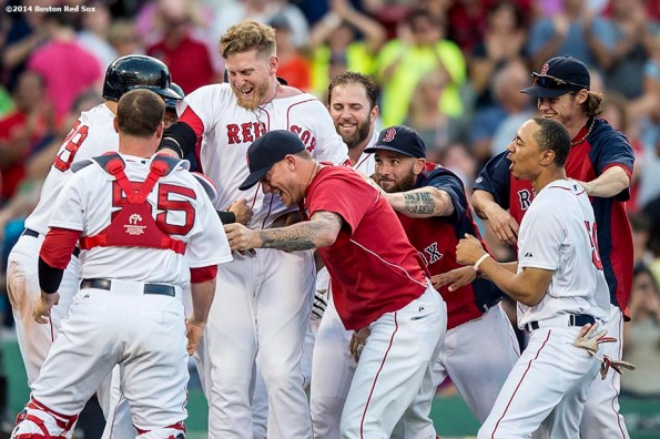 """""""Boston Red Sox teammates mob pinch hitter Mike Carp after hitting a game winning walk-off double during the tenth inning to defeat the Chicago White Sox 4-3 Thursday, July 10, 2014 at Fenway Park in Boston, Massachusetts."""""""