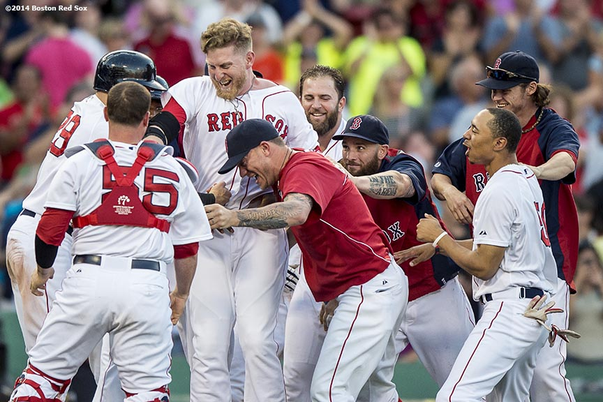 """Boston Red Sox teammates mob pinch hitter Mike Carp after hitting a game winning walk-off double during the tenth inning to defeat the Chicago White Sox 4-3 Thursday, July 10, 2014 at Fenway Park in Boston, Massachusetts."""