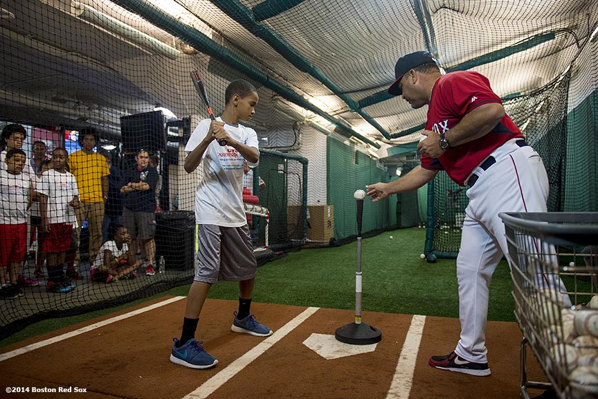 """Boston Red Sox hitting coach Victor Rodriguez holds batting practice with a member of the Boys & Girls Club during a CVS hitting clinic at Fenway Park in Boston, Massachusetts Friday, July 18, 2014."""