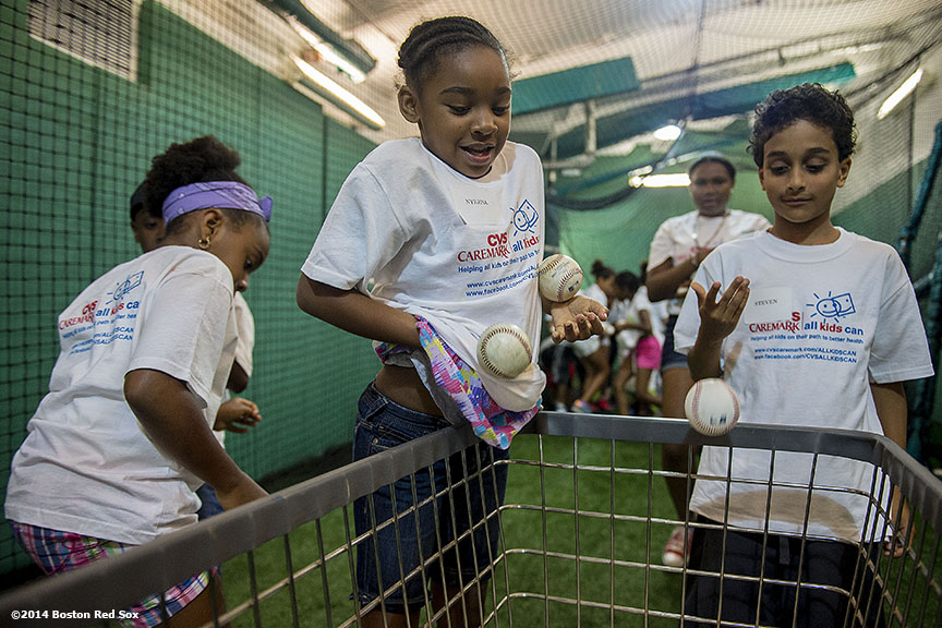 """Members of the Boys & Girls Club pick up baseballs after taking batting practice during a CVS hitting clinic at Fenway Park in Boston, Massachusetts Friday, July 18, 2014."""