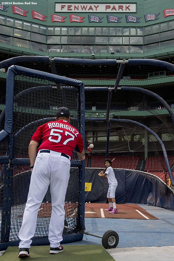"""Boston Red Sox hitting coach Victor Rodriguez tosses batting practice to a member of the Boys & Girls Club during a CVS hitting clinic at Fenway Park in Boston, Massachusetts Friday, July 18, 2014."""