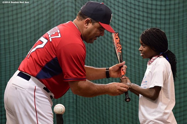 """Boston Red Sox hitting coach Victor Rodriguez give batting instructions to a member of the Boys & Girls Club during a CVS hitting clinic at Fenway Park in Boston, Massachusetts Friday, July 18, 2014."""