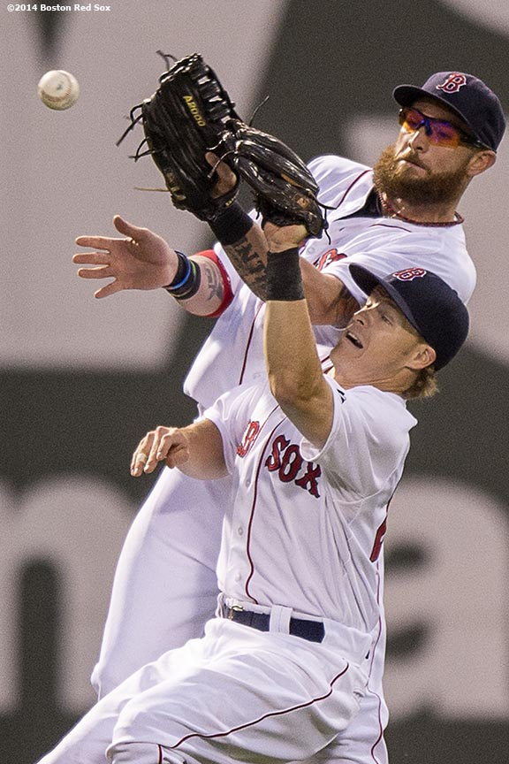 """Boston Red Sox shortstop Brock Holt and left fielder Jonny Gomes collide as they miscommunicate on a fly ball during the fourth inning of a game against the Kansas City Royals Saturday, July 19, 2014 at Fenway Park in Boston, Massachusetts. """