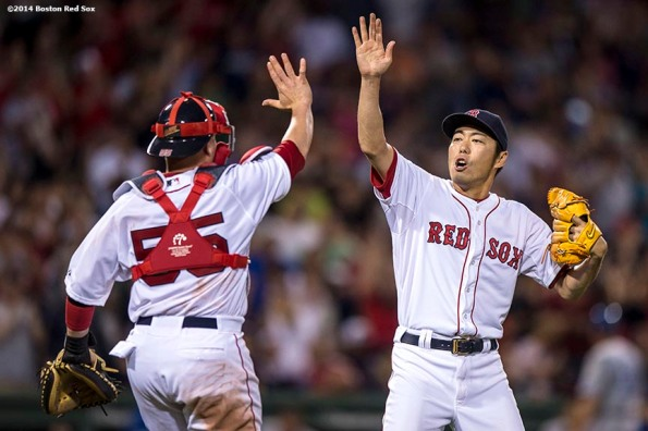 """Boston Red Sox pitcher Koji Uehara high fives catcher Christian Vazquez after recording the final out during the ninth inning of a game against the Kansas City Royals Saturday, July 19, 2014 at Fenway Park in Boston, Massachusetts. """