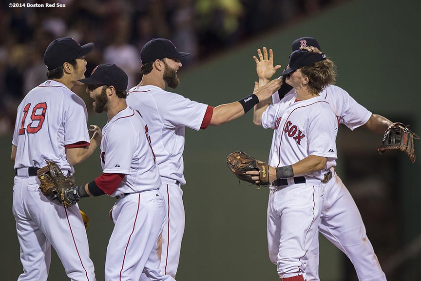 """""""Boston Red Sox first baseman Mike Napoli plays with the hat of shortstop Brock Holt after recording the final out during the ninth inning of a game against the Kansas City Royals Saturday, July 19, 2014 at Fenway Park in Boston, Massachusetts."""""""