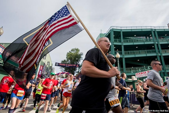Runners on Yawkey Way pass through the starting line of the Run to Home Base 10K course during the fifth annual Run to Home Base presented by New Balance at Fenway Park in Boston, Massachusetts Saturday, July 19, 2014.