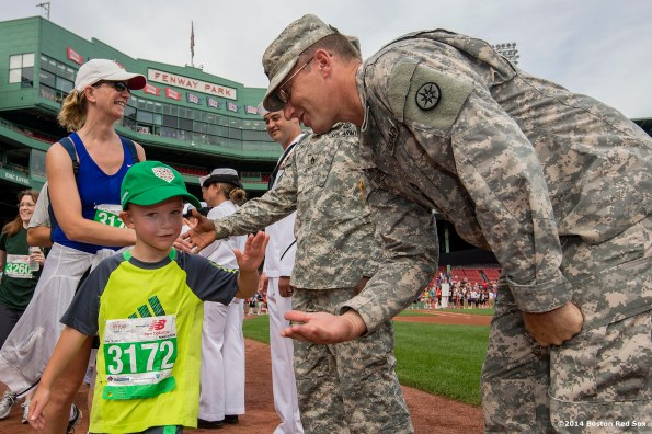 """A young race participant is congratulated by a member of the military after finishing a 10k race course during the fifth annual Run to Home Base presented by New Balance at Fenway Park in Boston, Massachusetts Saturday, July 19, 2014."""