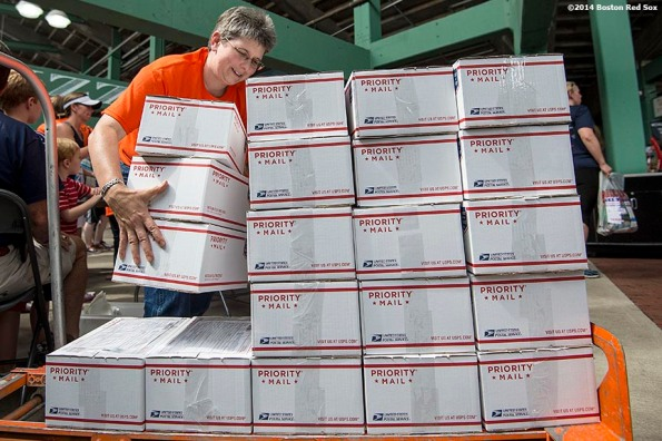 """""""A race volunteer stacks care packages prepared by race participants for active military members during the fifth annual Run to Home Base presented by New Balance at Fenway Park in Boston, Massachusetts Saturday, July 19, 2014."""""""