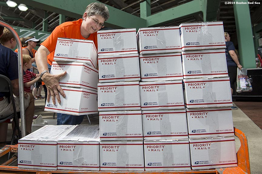 """A race volunteer stacks care packages prepared by race participants for active military members during the fifth annual Run to Home Base presented by New Balance at Fenway Park in Boston, Massachusetts Saturday, July 19, 2014."""