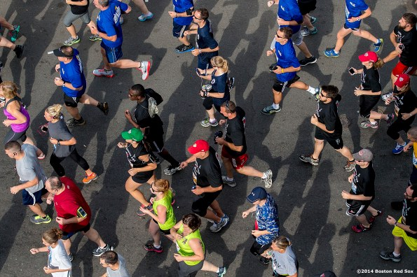 """Runners on Yawkey Way pass through the starting line of the Run to Home Base 10K course during the fifth annual Run to Home Base presented by New Balance at Fenway Park in Boston, Massachusetts Saturday, July 19, 2014."""