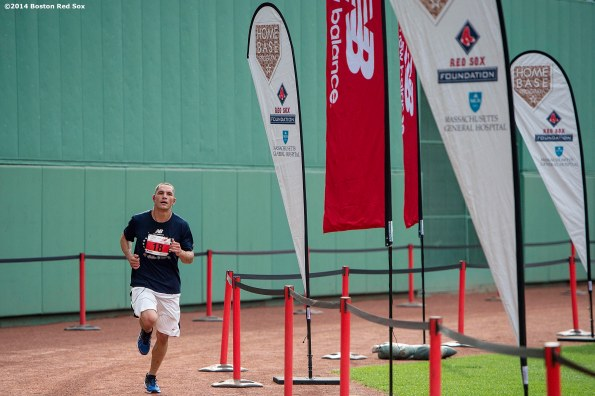 """""""A runner passes through the finish line in front of the Green Monster during the fifth annual Run to Home Base presented by New Balance at Fenway Park in Boston, Massachusetts Saturday, July 19, 2014."""""""