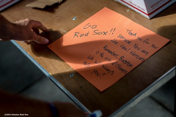 """A race participant writes a letter as he prepares a care package for active military members during the fifth annual Run to Home Base presented by New Balance at Fenway Park in Boston, Massachusetts Saturday, July 19, 2014."""