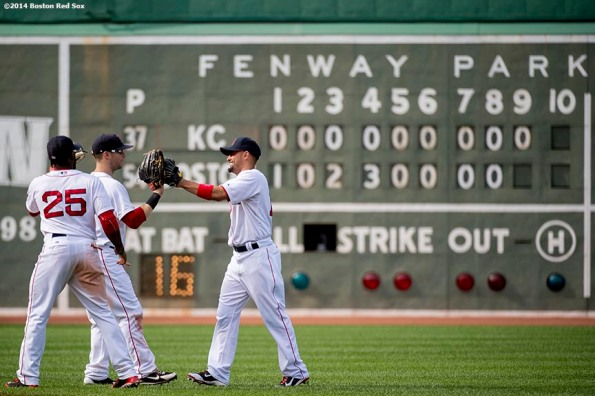 """Boston Red Sox outfielders Jackie Bradley Jr., Daniel Nava, and Shane Victorino high five each other after the Red Sox defeated the Kansas City Royals Sunday, July 20, 2014 at Fenway Park in Boston, Massachusetts. """