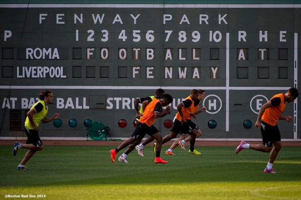 """Members of Liverpool FC run sprints in front of the Green Monster scoreboard during an open practice session before a match against AS Roma during Football at Fenway at Fenway Park in Boston, Massachusetts Tuesday, July 23, 2014. """