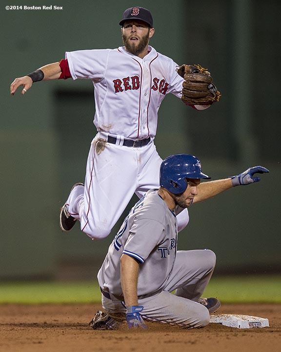 """""""Boston Red Sox second baseman Dustin Pedroia turns a double play during the seventh inning of a game against the Toronto Blue Jays at Fenway Park in Boston, Massachusetts Monday, July 28, 2014."""""""