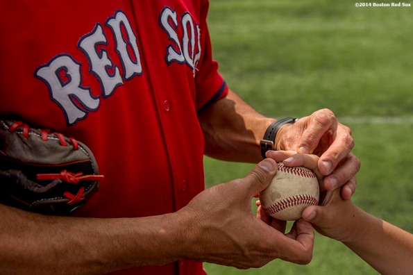 """""""Boston Red Sox pitching coach Juan Nieves shows a participant how to grip a baseball during a Sox Talk baseball clinic at Satori Field in East Boston, Massachusetts Wednesday, July 30, 2014."""""""
