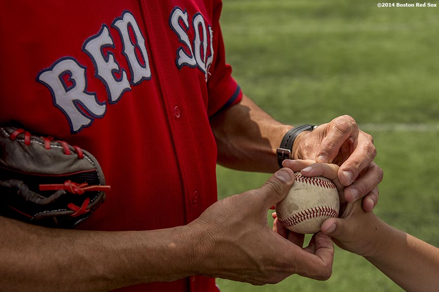 """Boston Red Sox pitching coach Juan Nieves shows a participant how to grip a baseball during a Sox Talk baseball clinic at Satori Field in East Boston, Massachusetts Wednesday, July 30, 2014."""