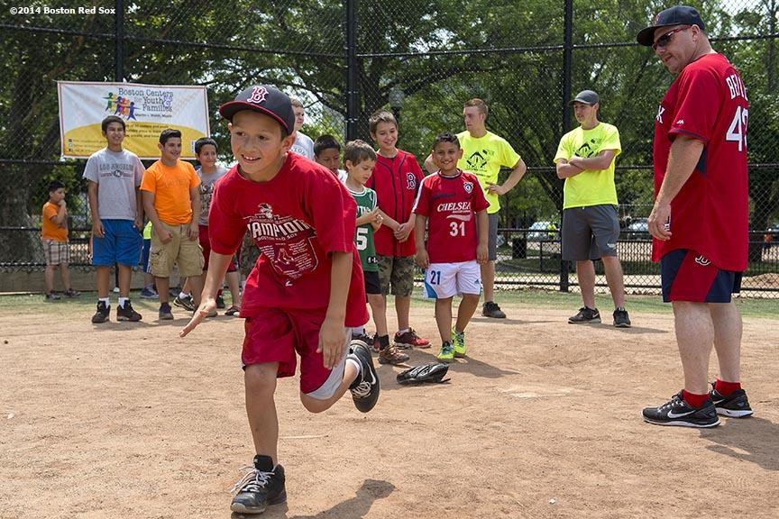 """Boston Red Sox first base coach Arnie Beyeler watches as a boy runs toward first base during a Sox Talk baseball clinic at Satori Field in East Boston, Massachusetts Wednesday, July 30, 2014."""