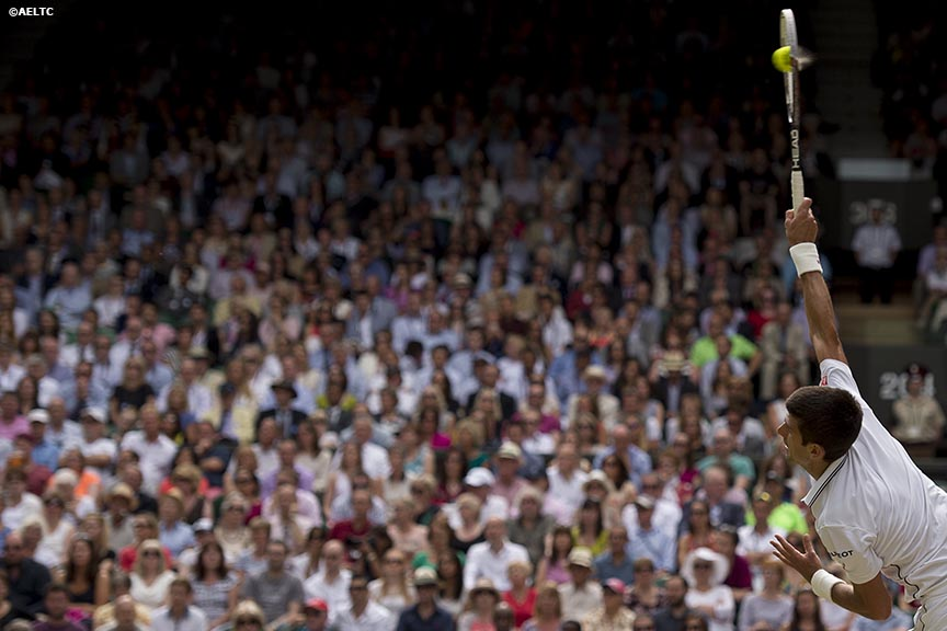 """Novak Djokovic serves during the gentlemen's singles final against Roger Federer at the All England Lawn and Tennis Club in London, England Sunday, July 6, 2014 during the 2014 Championships Wimbledon."""