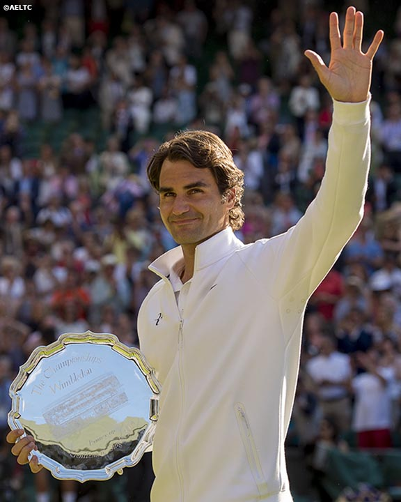 """Roger Federer waves to the crowd as he holds the runner up trophy after  being defeated by Novak Djokovic in the gentlemen's singles final at the All England Lawn and Tennis Club in London, England Sunday, July 6, 2014 during the 2014 Championships Wimbledon."""