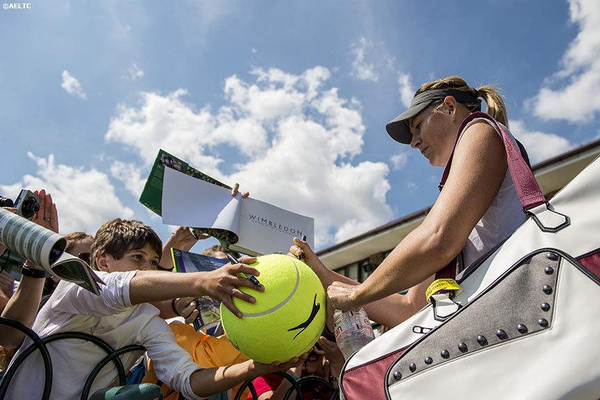 """Maria Sharapova signs autographs for fans at the All England Lawn and Tennis Club in London, England Tuesday, July 1, 2014 during the 2014 Championships Wimbledon."""