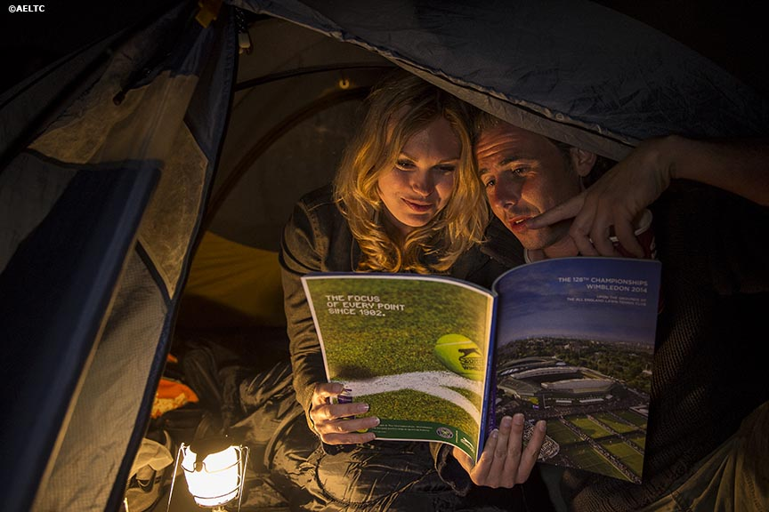 """Fans read a Wimbledon program as they camp out in a tent in the queue at the All England Lawn and Tennis Club in London, England Tuesday, July 1, 2014 during the 2014 Championships Wimbledon."""
