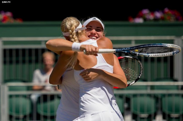 """Timea Babos and Kristina Mladenovic celebrate after defeating Andrea Petkovic and Magdalena Rybarikova at the All England Lawn and Tennis Club in London, England Friday, July 4, 2014 during the 2014 Championships Wimbledon."""