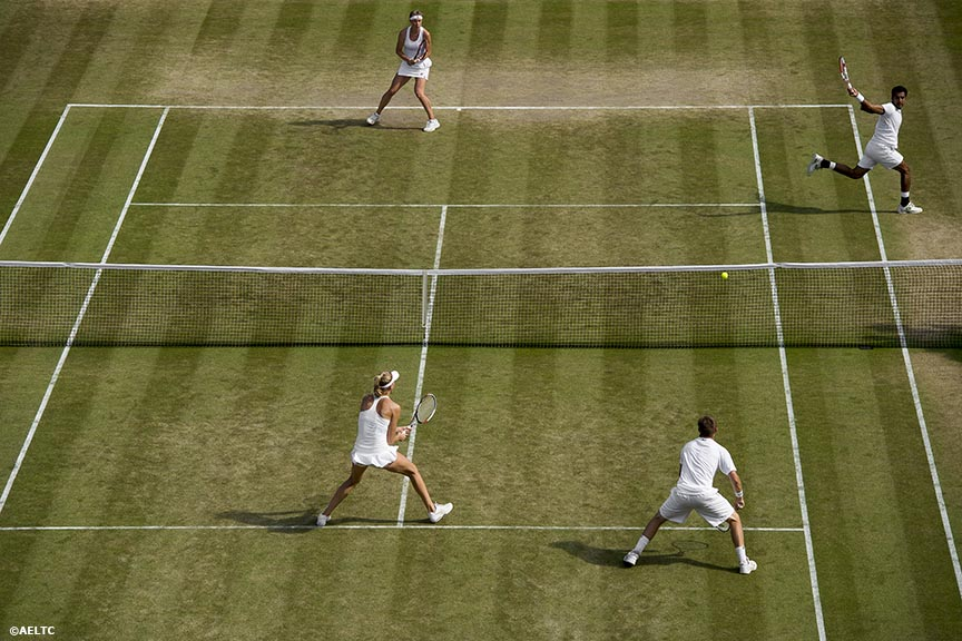 """Aisam Qureshi hits a forehand alongside partner Vera Dushevina during a mixed doubles match against Neal Skupski and Naomi Broady at the All England Lawn and Tennis Club in London, England Friday, July 4, 2014 during the 2014 Championships Wimbledon."""