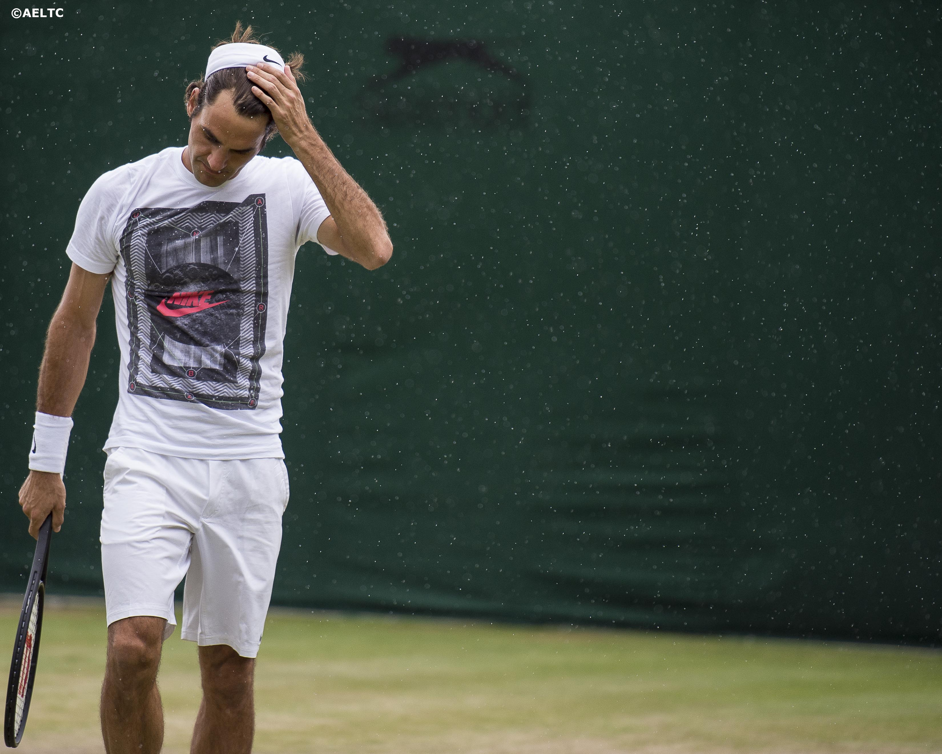"""""""Roger Federer removes his headband as rain falls during a practice session at the All England Lawn and Tennis Club in London, England Saturday, July 5, 2014 during the 2014 Championships Wimbledon."""""""