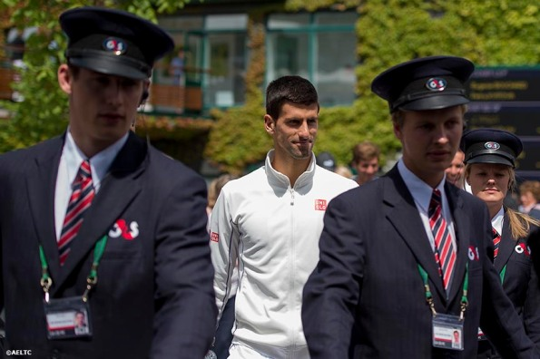 """Novak Djokovic is escorted by security members before a practice session at the All England Lawn and Tennis Club in London, England Saturday, July 5, 2014 during the 2014 Championships Wimbledon."""