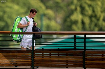 """Andy Murray walks across a bridge as he exits the grounds of the All England Lawn and Tennis Club after losing to Grigor Dimitrov in the quarter-finals Wednesday, July 2, 2014 during the 2014 Championships Wimbledon."""